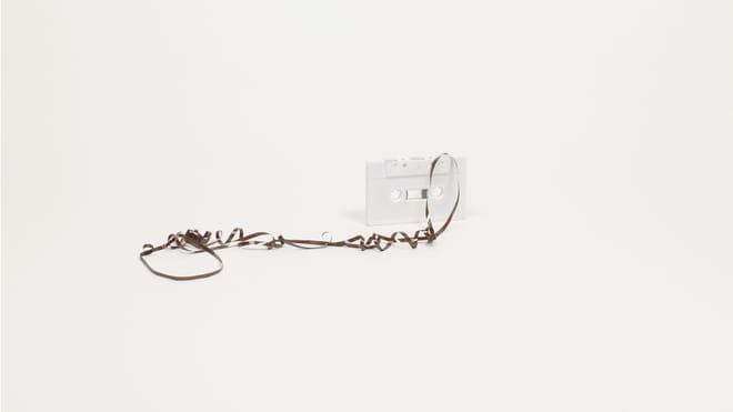 Beeld uit de serie Foley Objects van Finse kunstenares Jonna Kina. Voor deze serie fotografeerde Kina alledaagse dingen die gebruikt worden om geluidseffecten voor films te maken. Op deze foto zien we een casettebandje, met de tape er uit getrokken. Het onderschrift is: leaves of grass