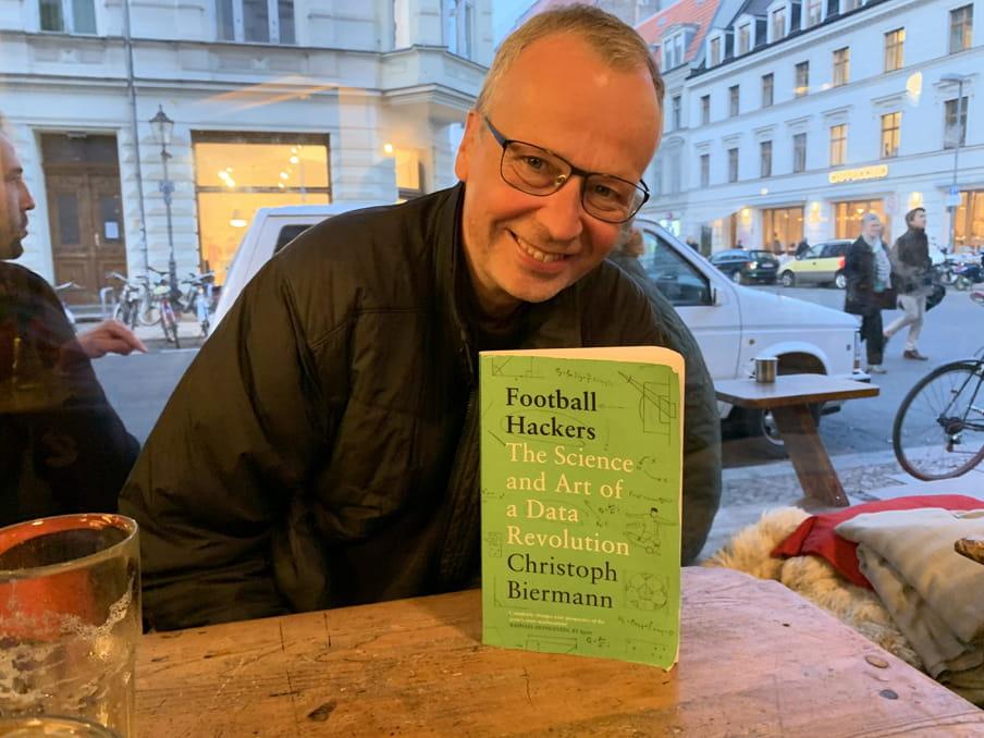 Journalist Christoph Biermann poseert met zijn boek 'Football Hackers' in een café in Berlijn-Mitte.