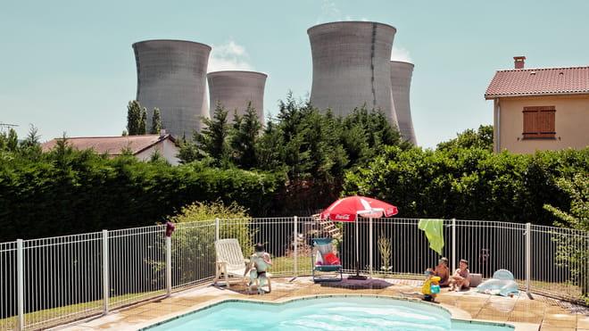 Foto van Italiaanse fotograaf Andrea Pugiotto. Op de voorgrond een zwembad in de achtertuin van een Frans gezin, daar vlak achter 4 grote koeltorens van een energie centrale.