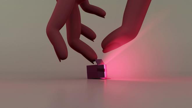 Hand die een licht gevend doosje pakt