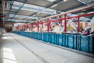 Een foto van een grote loods met een rij blauwe containers, hierachter zijn lopende banden met kleding te zien.