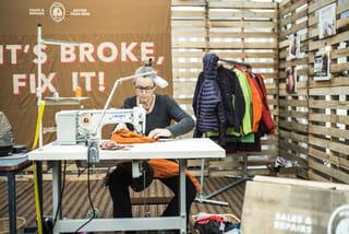 Een medewerker van Patagonia repareert een kledingstuk achter de naaimachine.