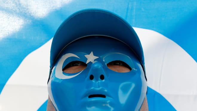 Een Oeigoer moslim met een blauw masker op staat voor een blauw met witte vlag.