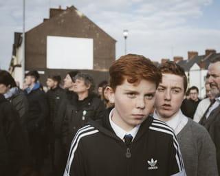 Een portret van een Katholieke jongen in een menigte bezoekers van de begrafenis van Martin McGuinness.