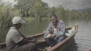 Twee vissers zitten op een open vissersbootje op het Izabal-meer bij El Estor in Guatamala.