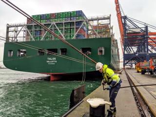 Een van de 'roeiers' legt een tros om een meerpaal. Links in beeld is de groene achtersteven van het containerschip Talos te zien. Rechts in beeld staan de kranen klaar om de containers van het schip te lossen