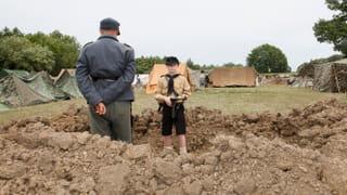 Jongetjes staat in een loopgraaf tijdens het naspelen van een oorlogssituatie