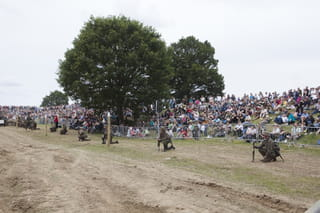 Publiek tijdens het naspelen van een oorlog