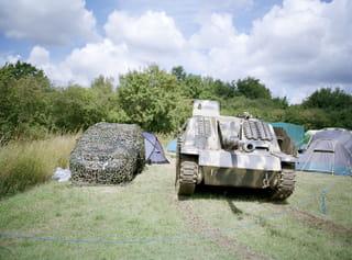 Auto met camouflage net erover, een neptank en op de achtergrond tentjes