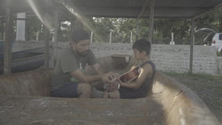 Carlos Choc en zijn zoontje zitten in een vissersboot, die aan wal ligt. Carlos leert zijn zoontje gitaar spelen.