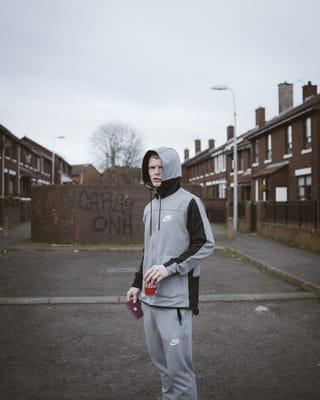 Een jongen gekleed in grijs joggingpak poseert met een Iers paspoort dat hij op straat heeft gevonden in Belfast. In zijn andere hand een blikje Cola.