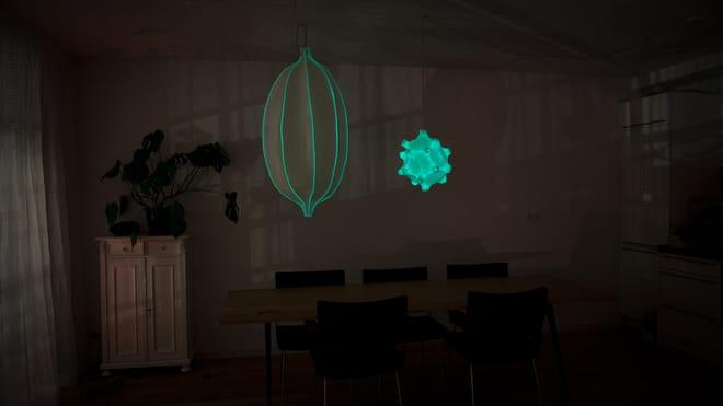 Foto van een woonkamer bij nacht. Boven de eettafel hangen twee glow in the dark lampen.