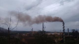 Rode rook komt uit de schoorstenen van de ijzerertsmijn in El Estor.