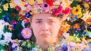 Een filmstill van een karakter uit de film Midsommar die lijkt te gaan huilen omringd door kleurige bloemen.