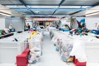 Een foto van witte bakken en plastic zakken in een grote industriële ruimte waar mensen tussen aan het werk zijn.