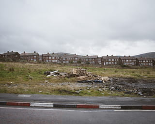 Rood, wit en blauw geschilderde stoepen in Glenbryn Park, Belfast. Op de achtergrond zie je overblijfselen van een vreugdevuur.