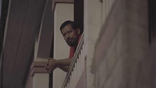 Een portret van Carlos Choc, genomen terwijl hij op de rand van zijn veranda leunt.