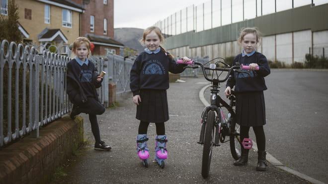 Drie meisjes voor hun huizen naast de vredesmuur in Iers Republikeins gebied, Belfast.