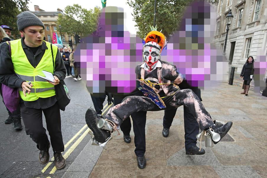 Een demonstrant van Extinction Rebellion wordt door twee politieagenten, die op de foto onherkenbaar zijn gemaakt, afgevoerd.