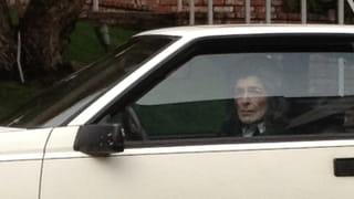 Een gepixelde foto van een vrouw die uit een autoraam kijkt vanuit een witte auto.