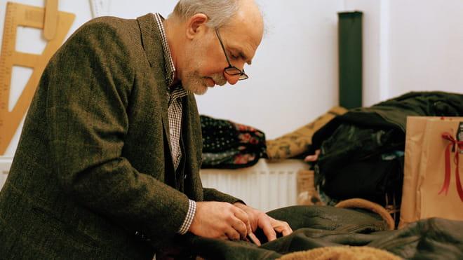 Foto van de Turkse kleermaker Atilla (van de winkel Amsterdam Tailors) aan het werk in zijn atelier. Atilla is bezig een leren jack te repareren.
