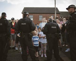 Vanaf hun rug zie je hoe politieagenten katholieke jongeren tegen houden tijdens een Oranjemars op 12 juli 2017 in Belfast.