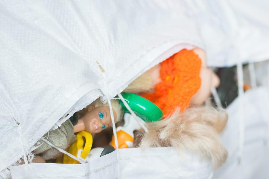 Foto van een witte zak waaruit het hoofd van een barbie puilt.