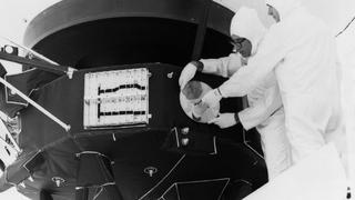 Zwart wit foto. 2 Technici van NASA gehuld in witte antistatische pakken bevestigen de gouden plaat aan de buitenkant van de ruimtesonde Voyager 2