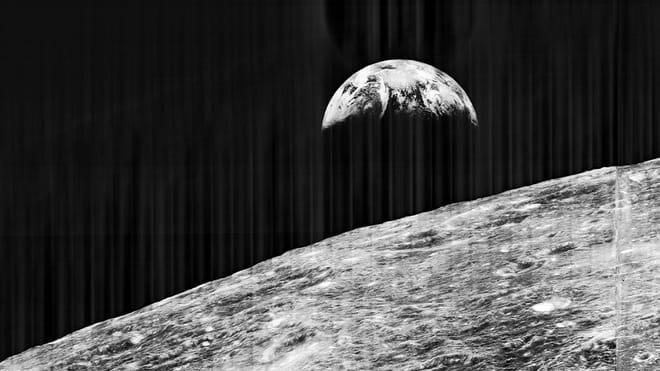 Zwart wit foto van de aarde, met op de voorgrond het maanoppervlak. Deze foto is genomen door de Lunar Orbiter 1, die het maanoppervlak in kaart moest brengen voor de Apollo landingen.