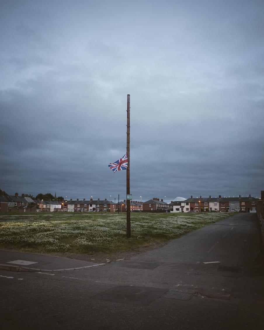 Een vlaggenmast met een Britse vlag op halfstok voor een wijk in Belfast.