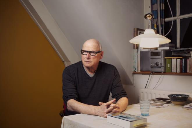 Portret van Oek de Jong aan een tafel in zijn woonkamer.