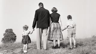 Een foto uit de jaren 50 van twee volwassenen en twee kinderen die elkaars handen vasthouden. Je ziet enkel de achterkant van alle mensen in het beeld.