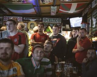 Een groepje Katholieke voetbalsupporters die Celtic Glasgow aanhangen kijken een wedstrijd tegen de lokale Protestantse Linfield club, Belfast.