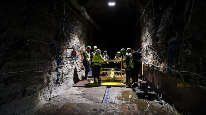 Groep mensen van pers staan in een ondergrondse opslag voor kernafval