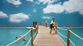 Mensen in zwemwaar voor een muur met daarop een afbeelding van de lucht